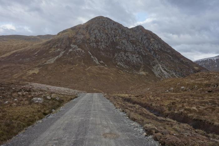 I follow a gravel road as skies turn grey